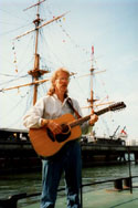 "Fred Gosbee with his 12-string guitar in front of HMS ""Warrior"", the first iron hulled ship, Portsmouth Naval Shipyard, Portsmouth, England. Credit: Julia Lane (1999). Photo permission and courtesy of Castlebay."